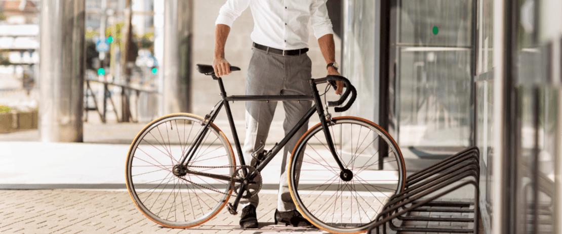 Dresskledd mann parkerer en sykkel utenfor kontoret